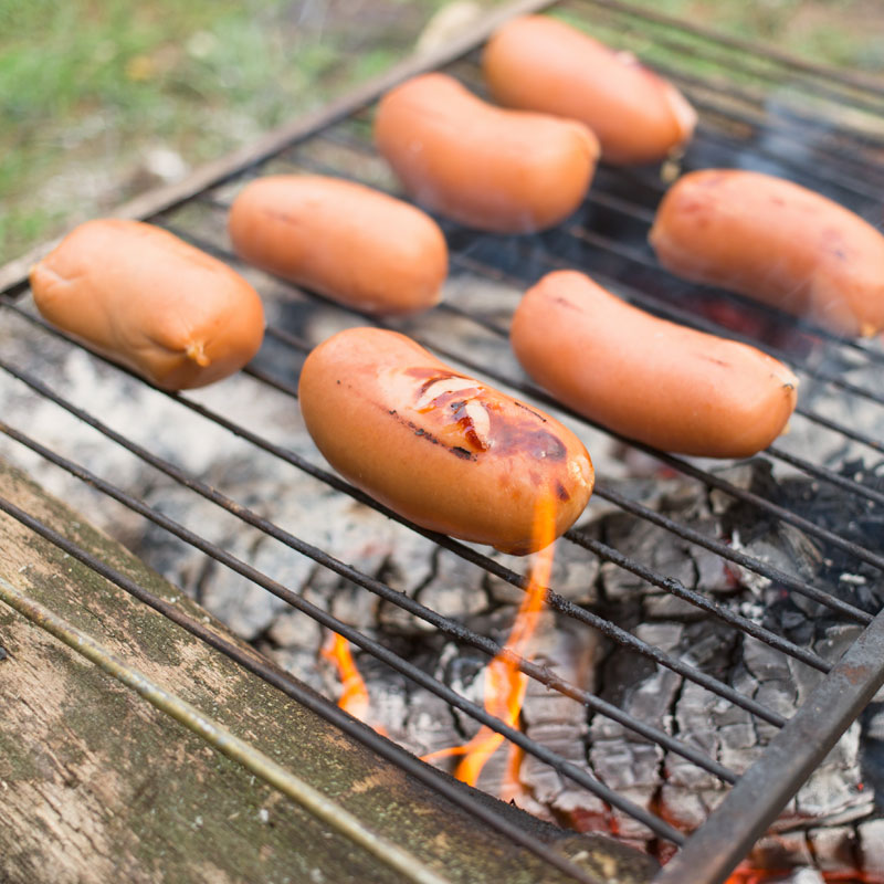 Cooking sausages over an open fire using a grill