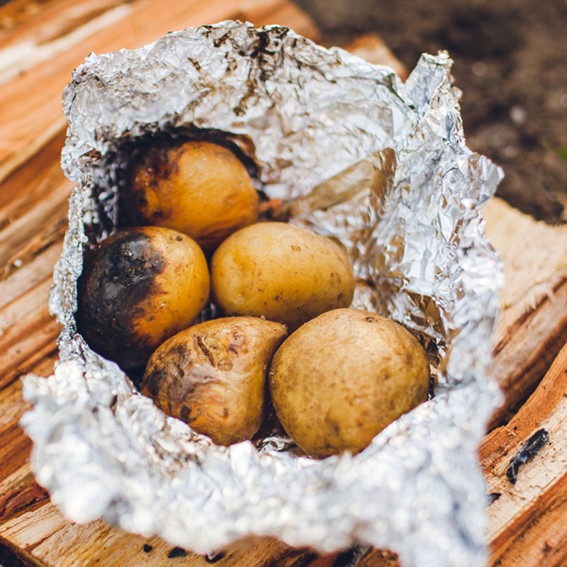 Potatoes baked in a camp fire wrapped in tinfoil